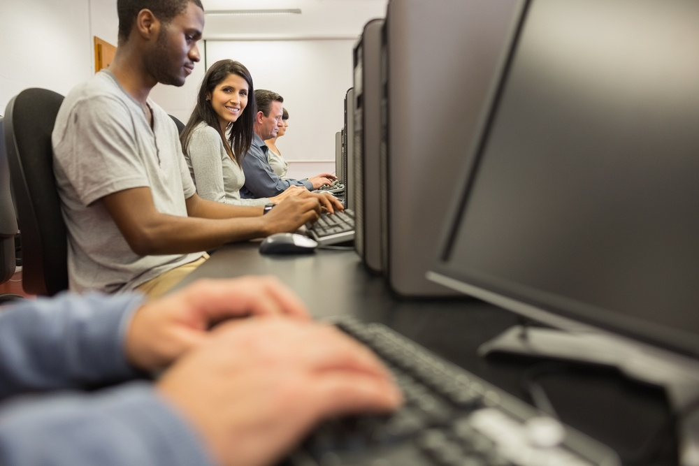 Woman looking up from computer class in college